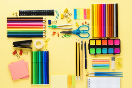 Set of various colorful school stationery and supplies on yellow background. Geometrically aligned flat lay. Copy space.