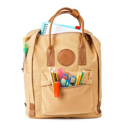 Brązowy plecak szkolny pełen różnych kolorowych artykułów papierniczych i materiałów eksploatacyjnych. Na białym tle.