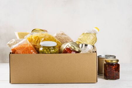 Various canned food, pasta and cereals in a cardboard box. Food donations or food delivery concept.