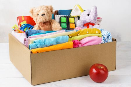 Colorful casual clothes, stationery and toys in a box for shipping or donation. Back to school concept.