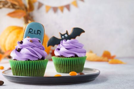 Halloween cupcakes decorated with homemade gingerbread cookies: tombstone and bat. Festive treats concept with copy space, selective focus.