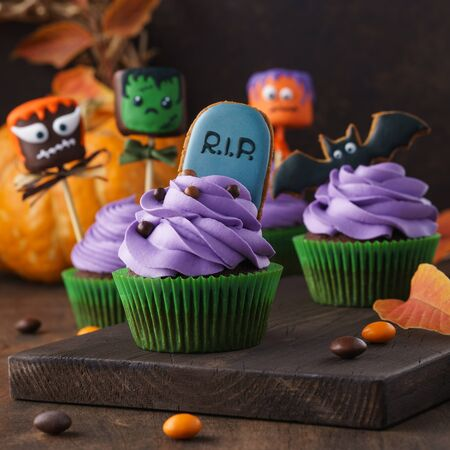 Set of festive Halloween cupcakes decorated with shaped gingerbread cookies and cake pops with funny monster faces. Dark background, selective focus.