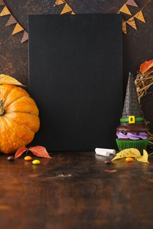 Fall season festive chalkboard background with pumpkin, leaves, and Halloween treats - candies and witch hat cupcake. Halloween sale mockup with blank space.