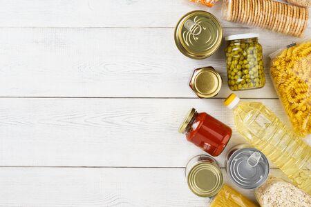 Ensemble de céréales crues, céréales, pâtes et conserves sur un tableau blanc. Espace de copie. Mise à plat. Banque d'images