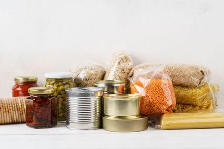 Varios alimentos enlatados y cereales crudos en una mesa. Conjunto de productos comestibles para cocinar, entrega o donación. Copie el espacio.