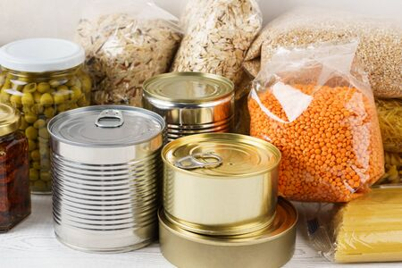 Various canned food and raw cereal grains on a table. Set of grocery goods for cooking, delivery or donation.