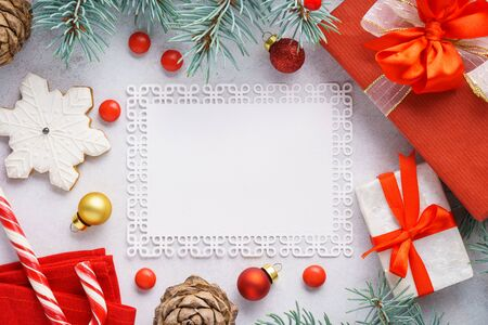 Christmas background with copy space. Xmas decorations - red and golden festive balls, gift box, fir-tree branches, cookies and candy. Overhead shot.