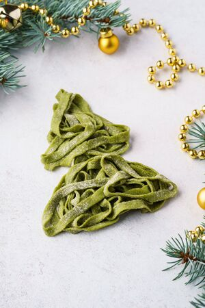 Christmas tree made of fresh homemade spinach pasta. Xmas background with fir-tree branches and decoration.