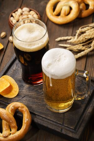Light and dark beer with various snacks - chips, pretzels and nuts on a dark wooden background.