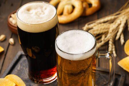 Zwei Gläser Bier - hell und dunkel mit verschiedenen Snacks im Hintergrund. Nahaufnahme.