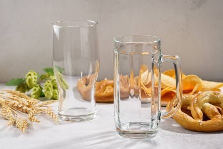 Clean and empty beer glass and a mug with various snacks around - pretzels and chips. Beer ingredients - hop and barley in the background.