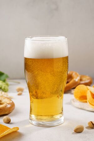 Light beer glass and snack variety around. Copy space.
