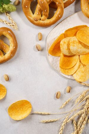 Assortment of various beer snacks - pretzels, chips and pistachios on light gray background with copy space.