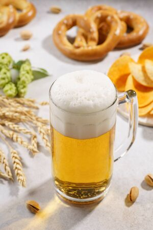A mug of draft beer and various snacks around - pretzels, chips and pistachios.