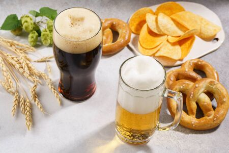 Light and dark beer with various snacks - chips, pretzels and nuts on a light gray background.