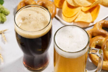 Two glasses of beer - light and dark with various snacks in the background. Close-up shot.