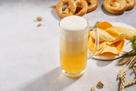 A mug of lager beer with german pretzels and chips on a light gray background. Copy space.