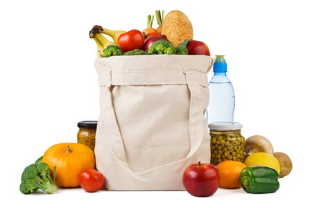 Reusable shopping tote bag full of various groceries - fruits, vegetables and bread. Isolated on white background. Imagens