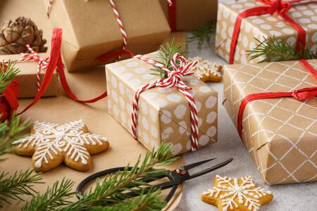 Handcrafted Christmas gift boxes, wrapping paper, cookies, red ribbon and twine. Winter holidays preparation. Xmas mood. Reklamní fotografie