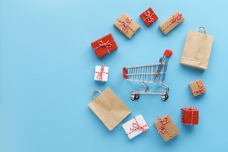 Various gift boxes and bags around a shopping cart on light blue background. Seasonal sales concept. Flat lay.