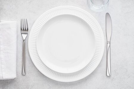 Table setting with white plates, glass, napkin and cutlery - fork and knife. Shot from above. Copy space on empty plate. Imagens