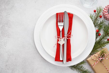 Christmas table setting with white plates, red napkin, cutlery - fork and knife, gift box and decoration. Xmas background with copy space.