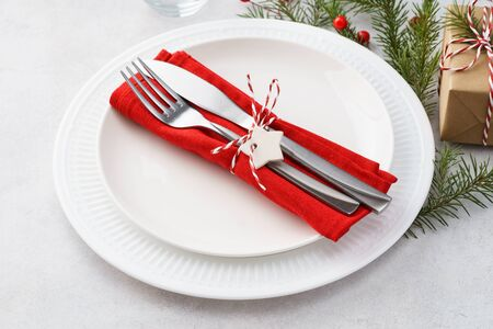 Christmas table setting with white plates, red napkin, cutlery - fork and knife, gift box and decoration. Xmas celebration.