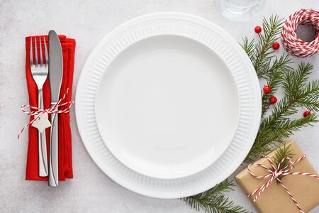 Christmas table setting with white empty plates, red napkin, cutlery - fork and knife, gift box and decoration. Xmas background with copy space. Imagens