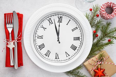 Christmas table setting with plate clock, napkin, cutlery - fork and knife, gift box and decoration. New Year or Christmas Eve celebration concept.