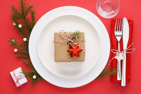 Christmas table setting with white plates, napkin, cutlery - fork and knife, gift box and decoration on red background. Xmas celebration concept.