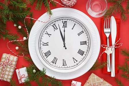 Christmas table setting with plate clock, napkin, cutlery - fork and knife, gift box and decoration on red background. New Year or Christmas Eve celebration concept.
