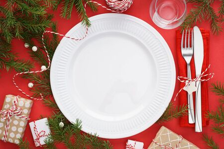 Christmas table setting with empty plate, fork and knife, gift boxes and decoration around. Red Xmas background with copy space.