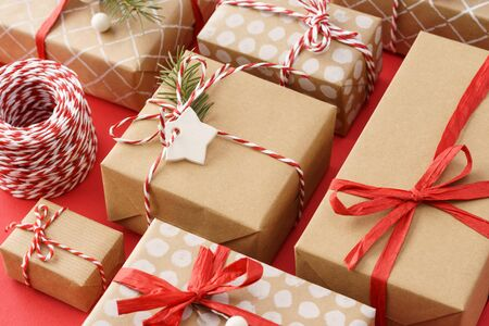 Paper wrapped gift boxes decorated with red ribbon and twine. Xmas sale concept.