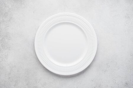 Empty round plate on light gray concrete background. Top view, copy space.