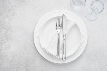 Restaurant table setting with white plates, glasses and cutlery. Light gray background with copy space. Overhead shot.