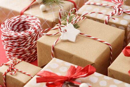 Paper wrapped gift boxes decorated with red ribbon and twine. Xmas sale concept. Close-up shot. Imagens