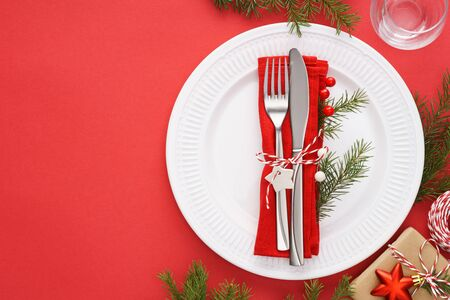 Christmas table setting with white plates, napkin and cutlery - fork and knife on red background. Xmas celebration concept with copy space.