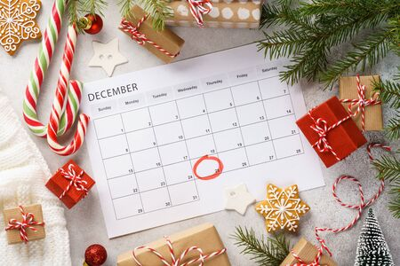 Planner page with Christmas gift boxes and decoration around. 25th of December marked with red circle on calendar. Xmas preparation concept. Imagens