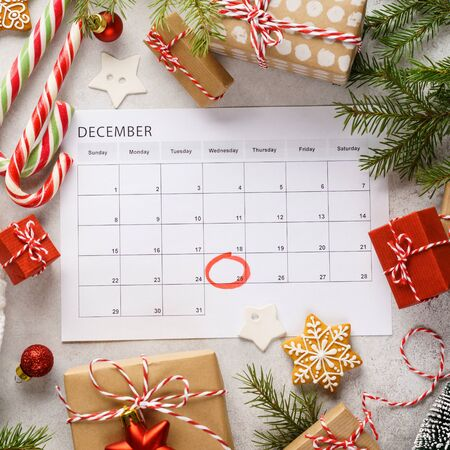 Planner page with Christmas gift boxes and decoration around. 25th of December marked with red circle on calendar. Xmas preparation concept. Banque d'images