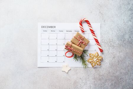 Planner page with Christmas gift boxes, cookies and decoration on light gray background. 25th of December marked with red circle on calendar. Xmas preparation concept. Copy space. Imagens