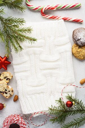 Christmas background with various festive cookies, candy and decoration around a white knitted fabric. Copy space.