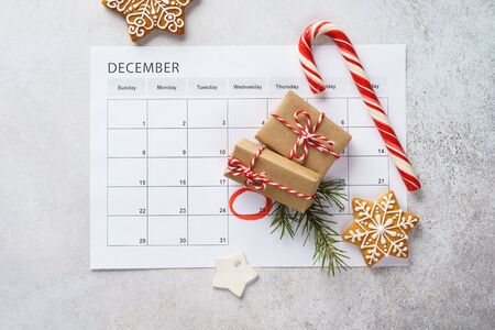 Planner page with Christmas gift boxes, cookies and decoration on light gray background. 25th of December marked with red circle on calendar. Xmas preparation concept.