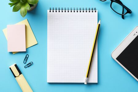 An open empty notepad, pen and tablet on a blue desk. Making a list or planning. Banque d'images