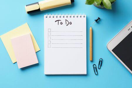 Un taccuino con la lista delle cose da fare su una scrivania blu con articoli di cancelleria e una pianta in vaso. Disposizione piatta. Copia spazio.