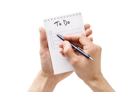 Man hands making a to-do list in a notebook. Isolated. Overhead shot.