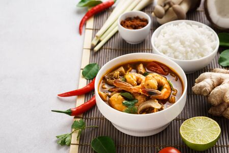 Tom Yum Goong or Tom Yum Kung spicy Thai soup and various ingredients for cooking. Space for recipe. Imagens