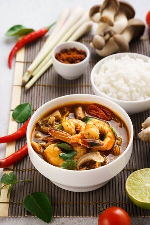 Tom Yum Goong spicy Thai soup with prawns, coconut milk and mushrooms. Tom Yum Kung served with rice. Traditional Thai food.