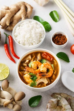 Traditional spicy Thai soup Tom Yum Goong or Tom Yum Kung and various ingredients around. Served with rice.