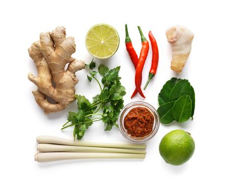 Set of Tom Yum soup basic ingredients - lemon grass, chilli peppers, galanga root, ginger, Tom Yam paste and kaffir lime leaves. Isolated on white. Imagens