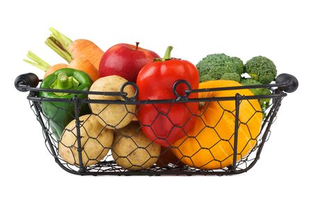 Various fresh vegetables and fruits in a wire basket. Isolated on white. Imagens